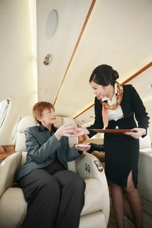 Flight attendant serving businesswoman with a glass of water Stock Photo