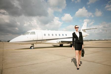 Businesswoman chodzenia na pasie startowym z prywatnego odrzutowca w tle