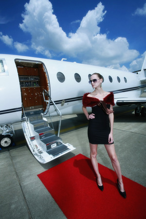 red carpet background: Woman standing on red carpet with private jet in the background