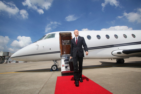 Businessman walking on red carpet upon exiting private jet Stock Photo