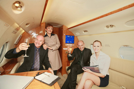 Business people in a private jet, businessmen holding up champagne glasses photo