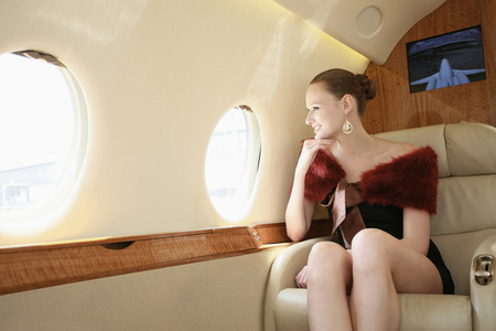 Woman looking out of the window in a private jet