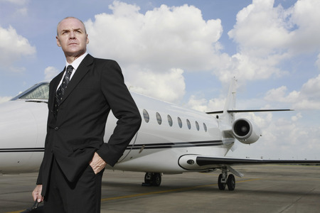 Businessman standing at private jet runway