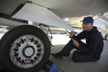 Mechanic examining tire of private jet