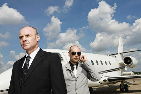 Businessman with his bodyguard and a private jet in the background