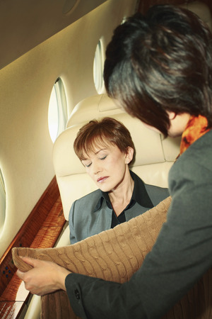 Flight attendant putting a blanket over sleeping businesswoman photo