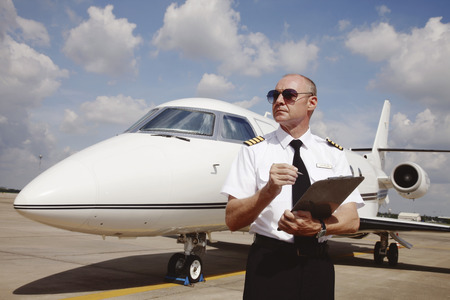 Pilot standing at runway holding a clipboard photo