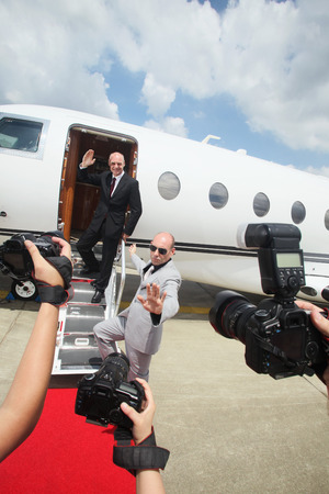 Businessman descending from private jet with his bodyguard, paparazzi taking photographs photo