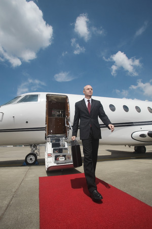 Businessman walking on red carpet upon exiting private jet photo
