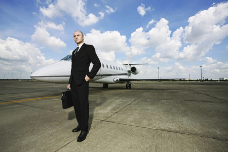 Businessman standing at private jet runway photo