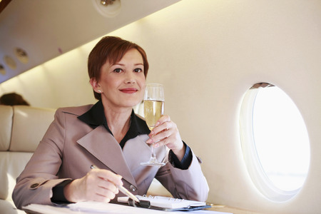 Businesswoman working on private jet while enjoying champagne photo