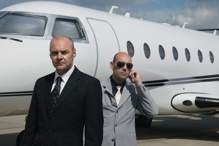 hearing protection: Businessman with his bodyguard and a private jet in the background