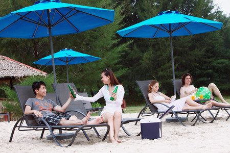 Men and women relaxing on lounge chairs at the beach photo