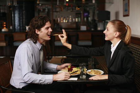 Businesswoman feeding businessman crisp photo