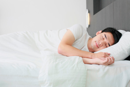cushion: Man sleeping on bed Stock Photo