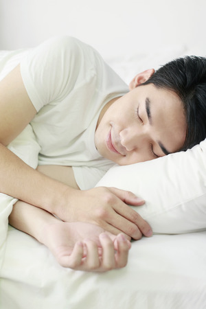 eyes closing: Man sleeping on bed Stock Photo