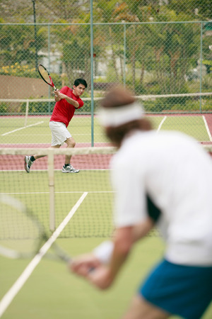 Man hitting tennis ball to his opponent photo