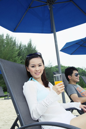 Man and woman relaxing on lounge chair at the beach photo