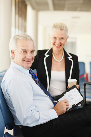 airport lounge: Businessman writing in organizer, businesswoman holding a cup of coffee in airport lounge Stock Photo