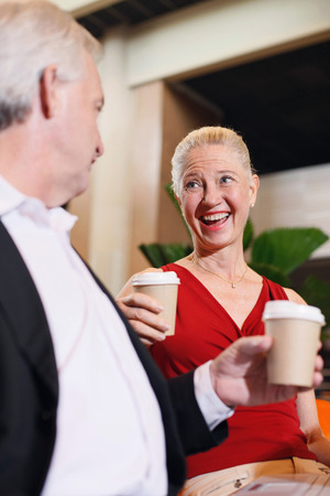 Businessman and businesswoman enjoying coffee in airport lounge photo