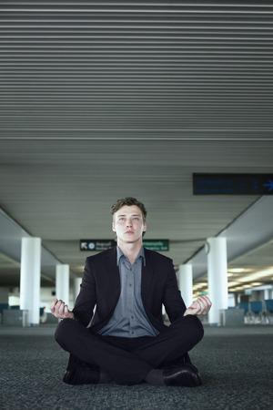 Businessman meditating in airport lounge