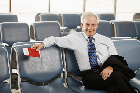 airport lounge: Businessman sitting in airport lounge holding his passport Stock Photo