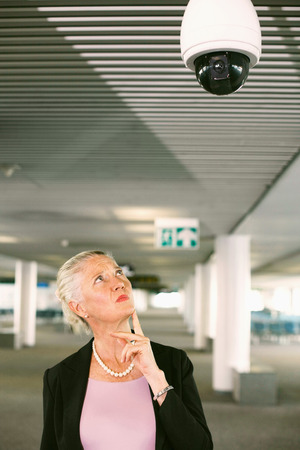 airport lounge: Businesswoman looking at security camera in airport lounge