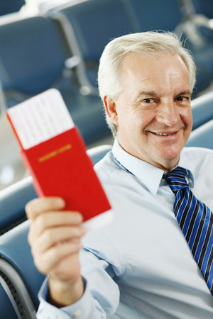 airport lounge: Businessman sitting in airport lounge showing his passport