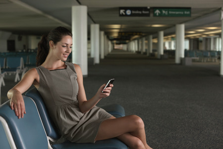 airport lounge: Businesswoman text messaging on phone in airport lounge Stock Photo