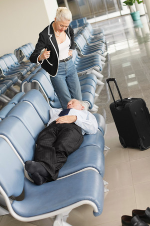 airport lounge: Businessman asleep on seat in airport lounge, businesswoman standing over him pointing finger Stock Photo