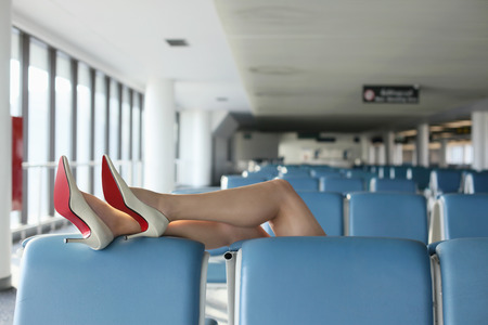 airport lounge: Businesswoman resting her legs on seat in airport lounge