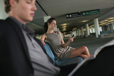 Businesswoman text messaging on phone in airport lounge, businessman reading newspaper photo