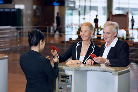 Biznesmen i businesswoman na lotnisku odprawy z ich paszportów