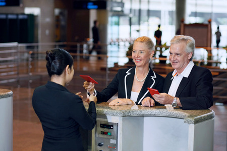 Businessman and businesswoman at the airport check-in counter with their passports
