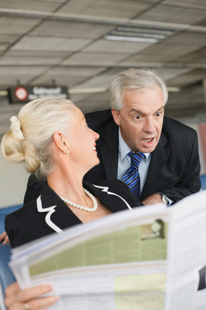 Businesswoman reading newspaper in airport lounge, businessman reading behind her photo
