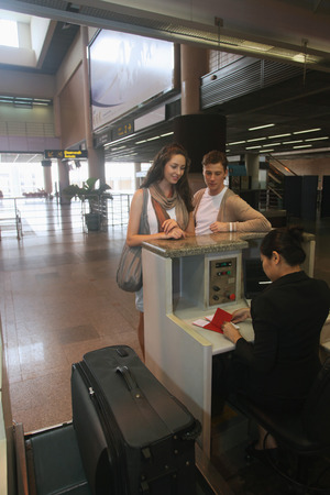 airport check in counter: Airline check-in attendant checking passports of man and woman at the airport check-in counter