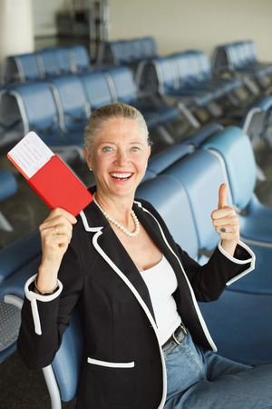 airport lounge: Businesswoman showing her passport and thumbs up in airport lounge Stock Photo