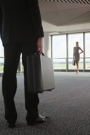 airport lounge: Businessman and businesswoman waiting for their flight in airport lounge