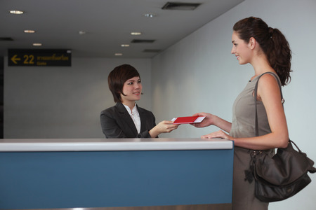 Airline check-in attendant returning businesswoman's passport at the airport check-in counter