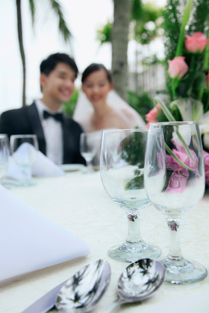Bride and groom at their wedding reception, focus on\ foreground