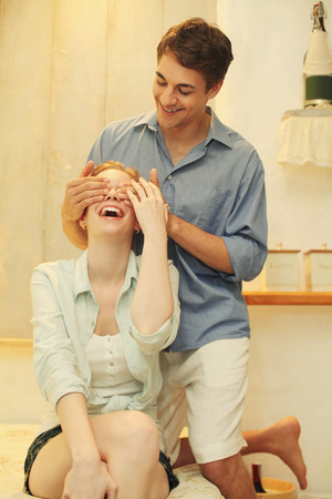central european ethnicity: Man covering womans eyes giving her surprises Stock Photo
