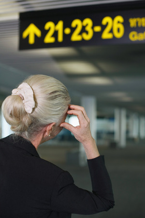 airport lounge: Businesswoman looking at directional sign in airport lounge