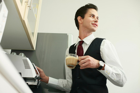 Businessman making coffee in the office pantry photo