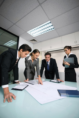 mature mexican: Business people reviewing blueprints together