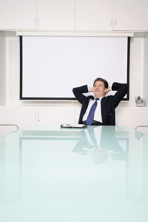 Businessman daydreaming in conference room photo