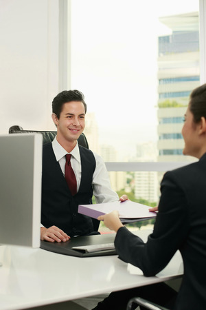 Businesswoman passing document to businessman Stock Photo