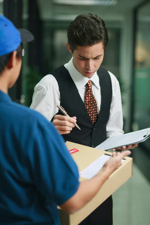 Businessman checking before signing for package photo