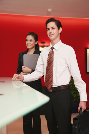 standing reception: Businessman and businesswoman standing at the reception counter Stock Photo