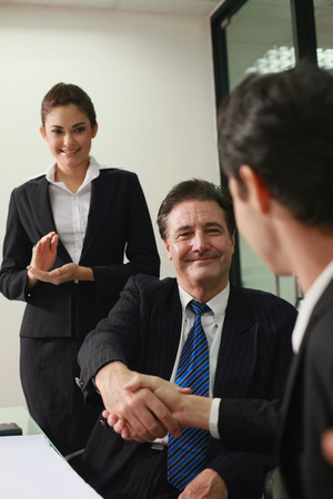Businessmen shaking hands, businesswoman applauding photo