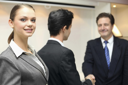 mature mexican: Businesswoman smiling, businessmen shaking hands in the background